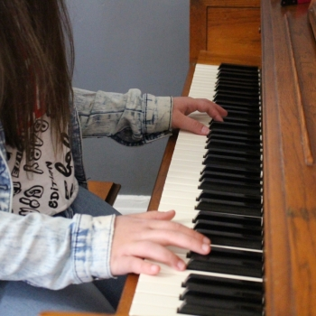Arelis playing piano, close-up on hands