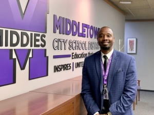 Mr. Kee Edwards standing in front of MCSD logo sign